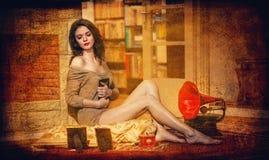 在葡萄酒风景的照片框架围拢的一台红色留声机附近的美丽的性感的妇女。女孩画象亭亭玉立的适合短小礼服的 免版税库存照片