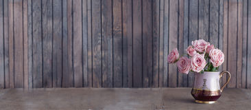 在葡萄酒水罐的桃红色玫瑰 图库摄影