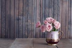 在葡萄酒水罐的桃红色玫瑰 库存照片