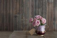在葡萄酒水罐的桃红色玫瑰 免版税库存照片