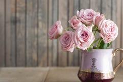 在葡萄酒水罐的桃红色玫瑰 库存图片