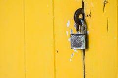 在葡萄酒黄色门的生锈的挂锁 免版税库存照片