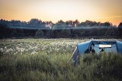 在葡萄酒colo的野营假日期间在夏天农村领域与雾和森林的野营的帐篷背景的和橙色日落天空 库存图片