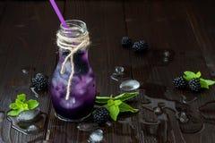 在葡萄酒eco的刷新的黑莓汁称呼在土气黑暗的木桌上的瓶 与冰和薄菏的冷的夏天莓果饮料 免版税库存照片