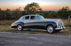 在葡萄酒luxery大型高级轿车后的日落在得克萨斯乡下公路 图库摄影