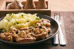 在葱调味汁烹调的猪里脊肉服务用土豆泥 图库摄影