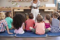 在蒙台梭利学校读对孩子的老师在故事时间 免版税库存照片