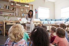 在蒙台梭利学校读对孩子的老师在故事时间 免版税图库摄影