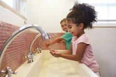 在蒙台梭利学校洗涤的手的学生在洗手间 库存照片