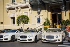 在蒙地卡罗赌博娱乐场前面停放的三辆白色本特利汽车 库存照片