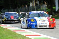 在蒙扎跑道的堡侍捷997和Ferrari 458 免版税库存图片