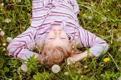 在蒲公英草甸的逗人喜爱的孩子 免版税库存照片