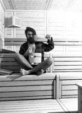 在蒸汽浴的休息 木浴的英俊的有胡子的人与桶和匙子 库存图片