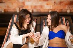 在蒸汽浴的木懒人放置的泳装的两美丽的少女谈论新闻,当调查电话时 免版税库存照片