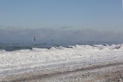 在蒸汽的密歇根湖上的一个灯塔在一个零度以下的冬天 免版税图库摄影