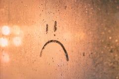 在蒸汽的窗口的哀伤的微笑题字 图库摄影