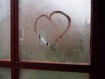 在蒸汽的窗口的心脏 库存图片