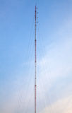 在蓝天的无线电天线连接与云彩 库存图片