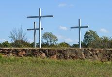 在蓝天前面的3个白合金十字架与白色云彩 免版税库存图片