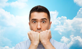 在蓝天和云彩背景的害怕的人 免版税库存图片