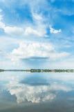 在蓝天和它的大云彩反射在河 库存照片