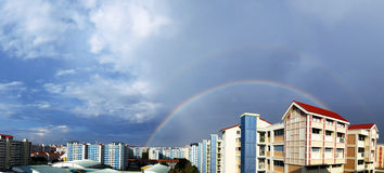 在蓝天和居住区的双重彩虹 免版税库存照片