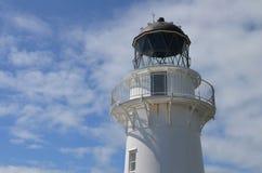 在蓝天和有些云彩前面的白色灯塔 图库摄影