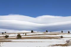 在蓝天和沙漠多雪的小山的惊人的云彩 图库摄影