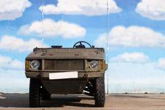 在蓝天演示墙壁前面的老军事卡车吉普立场 免版税库存图片