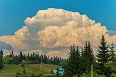 在蓝天的一朵巨大的白色云彩垂悬在山村 库存照片