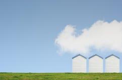在蓝天的三个海滩小屋 免版税库存图片