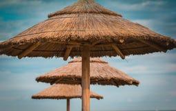 在蓝天的三把秸杆海滩遮阳伞 图库摄影