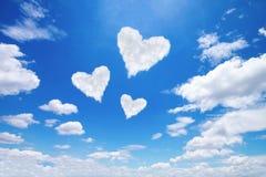 在蓝天的三朵白色心形的云彩 库存图片