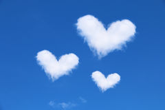 在蓝天的三朵白色心形的云彩 库存照片