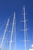 在蓝天的三白色游艇帆柱 图库摄影