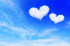 在蓝天的两朵心形的云彩华伦泰背景的 免版税库存图片