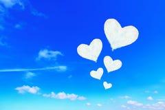 在蓝天的五朵白色心形的云彩 库存照片