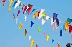 在蓝天的五颜六色的旗布旗子 免版税库存图片