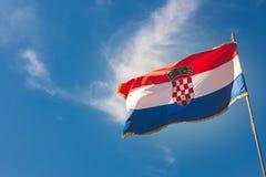 在蓝天的克罗地亚旗子与轻的云彩 免版税库存照片