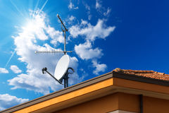 在蓝天的卫星盘和天线电视 免版税图库摄影