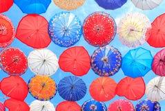 在蓝天的多彩多姿的伞 免版税库存图片