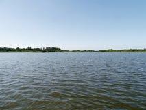 在蓝天的宽广的河场面 免版税库存图片