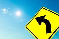 在蓝天的弯曲的公路交通符号 免版税库存图片