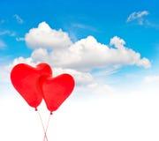 在蓝天的心形的红色气球 重点 图库摄影