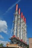 在蓝天的抽烟的工厂管子 免版税图库摄影
