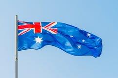 在蓝天的挥动的五颜六色的澳大利亚旗子 库存照片
