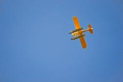 在蓝天的明亮的黄色平面飞行 免版税库存照片