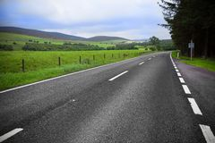 在蓝天的柏油路通过绿色领域和云彩 图库摄影