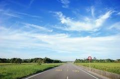 在蓝天的柏油路通过绿色领域和云彩在夏日,极限速度是50,台湾 免版税库存照片