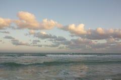 在蓝天的桃红色云彩在绿松石海 库存图片